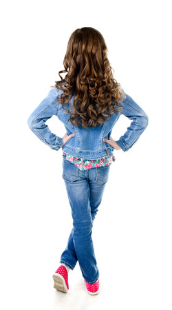 Portrait of adorable little girl in jeans standing back isolated on a white Stock Photo