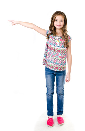 Cute little girl is pointing to the side isolated on a white