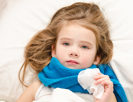 Sick little girl lying in the bed with scarf and tissue for blowing nose