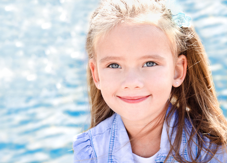 Outdoor portrait of cute little girl near the sea in spring day Фото со стока