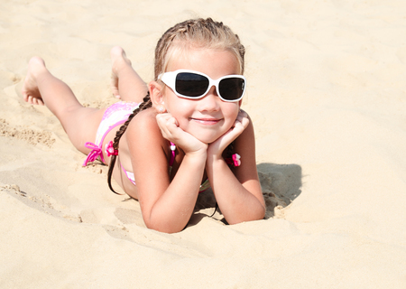 Happy cute little girl child in sunglasses lying on the sand on the beach Фото со стока