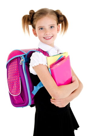 Portrait of smiling school girl child with backpack and books in uniform isolated on a white background Stock Photo