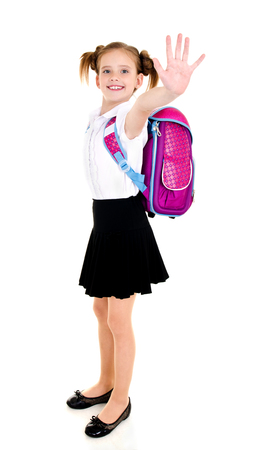 Smiling school girl child with backpack saying good bye isolated on a white background