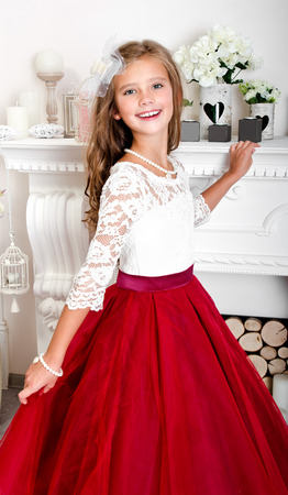 Adorable smiling little girl child in princess dress near the fireplace photo