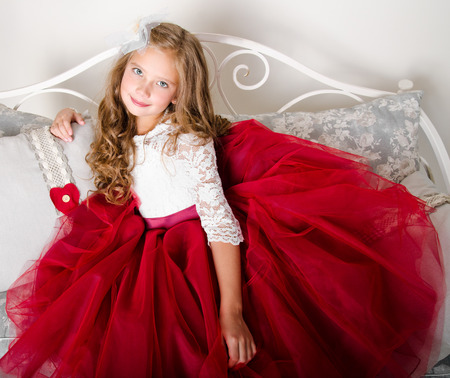 Adorable smiling little girl child in princess dress sitting on the sofa photo