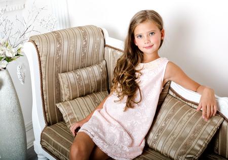 Schattig lachend meisje kind in prinses jurk zittend op de bank