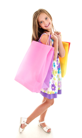 Adorable little girl child holding shopping colorful paper bags isolated on a white