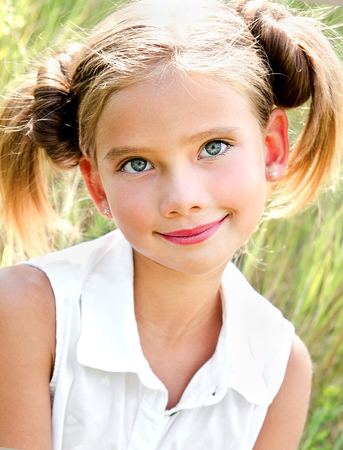 is green: Portrait of adorable smiling little girl child in dress outdoor in summer day Stock Photo