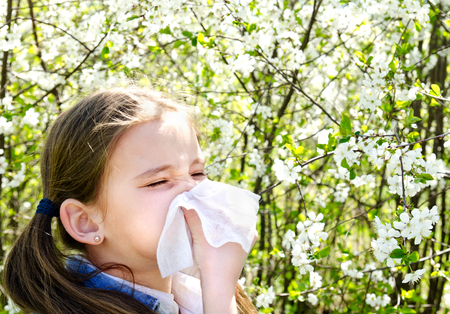 Little girl has allergy to spring blossoming and blowing her nose outdoor