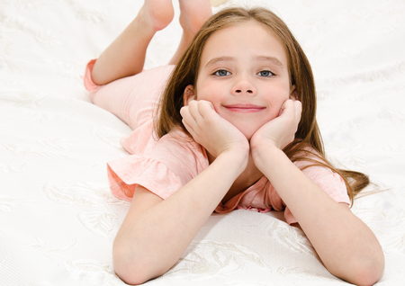 Adorable smiling little girl child is resting on a bed at home Standard-Bild