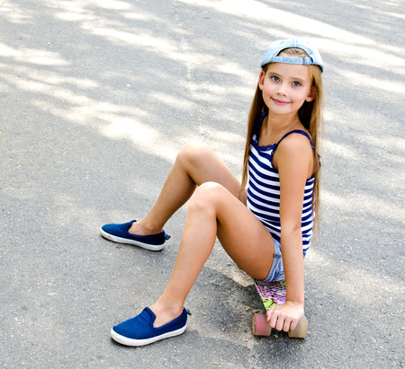 Adorable happy smiling  little girl child with skateboard outdoors in summer day