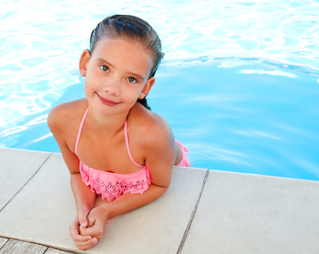 Cute smiling happy little girl child  in swimming pool in summer day