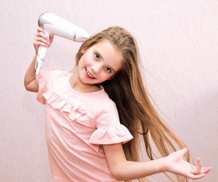 Cute smiling little girl child drying her long hair with hair dryer isolated Фото со стока