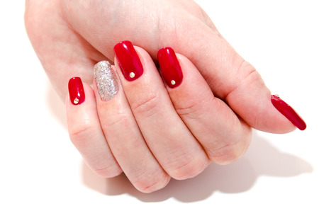 Woman's nails with beautiful red manicure fashion design with gems isolated on a white
