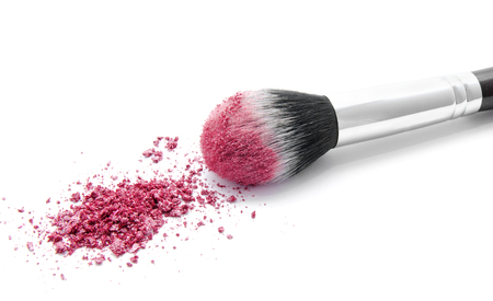 Professional makeup brush and colourful eye shadows isolated over white