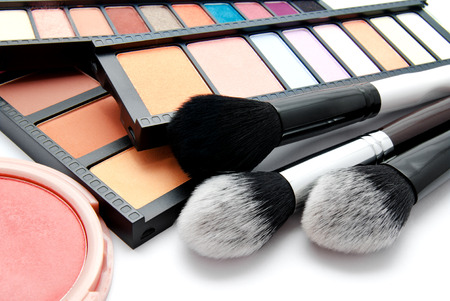 Various set of professional makeup brushes and palette of colourful eye shadows isolated over white