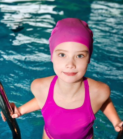 Portrait of cute smiling little girl child swimmer in pink swimming suit and cap in the swimming pool indoor 写真素材