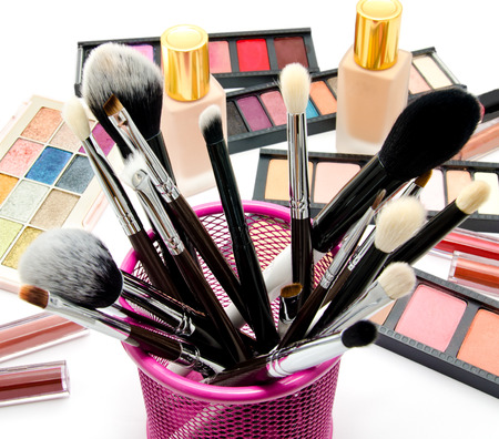 Various set of professional makeup brushes and cosmetics and palette of colourful eye shadows isolated over white background Stockfoto