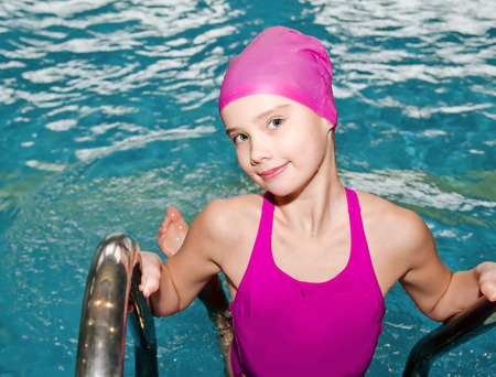 Portrait of cute smiling little girl child swimmer in pink swimming suit and cap in the swimming pool indoor Stock Photo