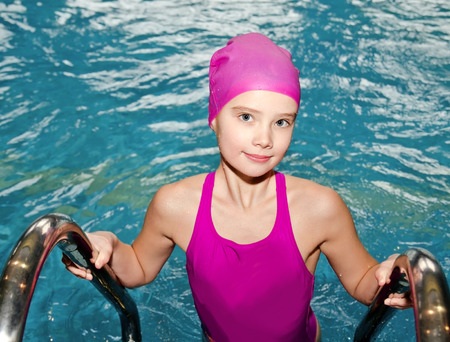 Portrait of cute smiling little girl child swimmer in pink swimming suit and cap in the swimming pool indoor Archivio Fotografico