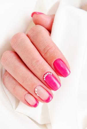 Uñas de mujer con un hermoso diseño de moda de manicura con gemas. Foto de archivo