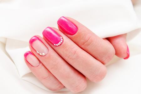 Ongles de femme avec un beau design de mode de manucure avec des pierres précieuses de couleur rose