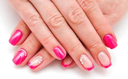 Uñas de mujer con un hermoso diseño de moda de manicura con gemas de color rosa. Foto de archivo