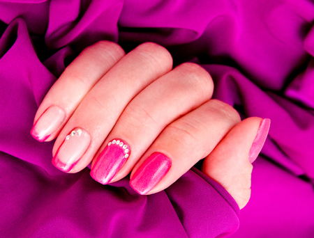 Womans nails with beautiful manicure fashion design with gems lilac color