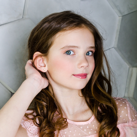 Portrait of adorable smiling little girl child schoolgirl with curl hair close up Reklamní fotografie - 123365438