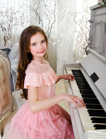 Portrait of adorable smiling little girl child schoolgirl with curl hair playing the piano