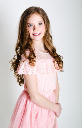 Portrait d'une adorable petite fille souriante écolière en robe de princesse avec des cheveux bouclés debout isolé sur un blanc Banque d'images