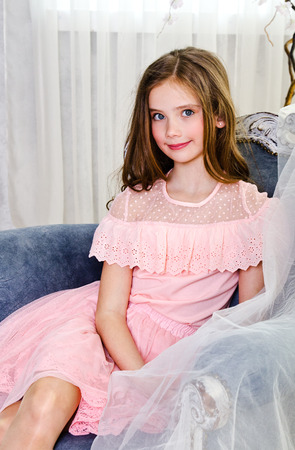 Portrait of adorable smiling little girl child schoolgirl in princess dress sitting in the chair