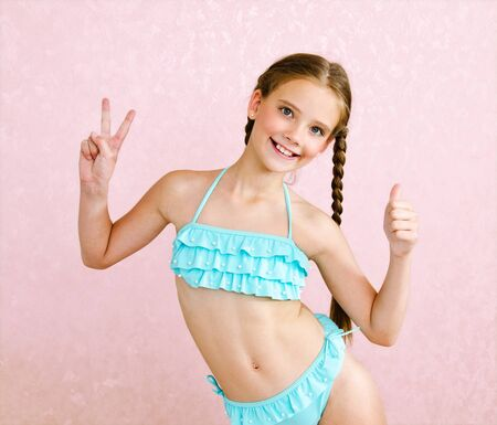 Portrait of cute smiling little girl child schoolgirl teenager in swimsuit and finger up isolated fashion concept