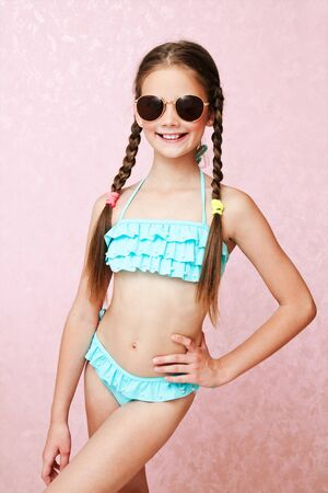 Portrait of cute smiling little girl child schoolgirl teenager in swimsuit and sunglasses isolated fashion concept