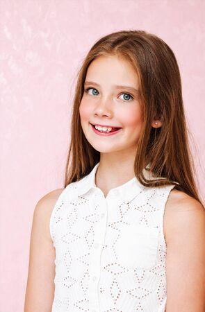 Retrato de adorable niña sonriente adolescente colegiala en vestido con pelo largo que se encuentran aisladas