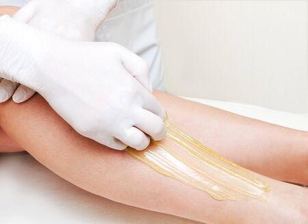 Esthéticienne cosmétologue épilation des jambes féminines dans le centre de spa salon de beauté épilation épilation concept de cosmétologie