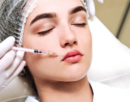 La esteticista médico cosmetóloga realiza el procedimiento de inyecciones faciales rejuvenecedoras para tensar y suavizar las arrugas.