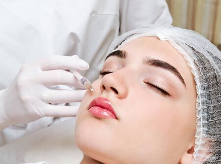 The doctor cosmetologist beautician makes the rejuvenating facial  injections procedure
