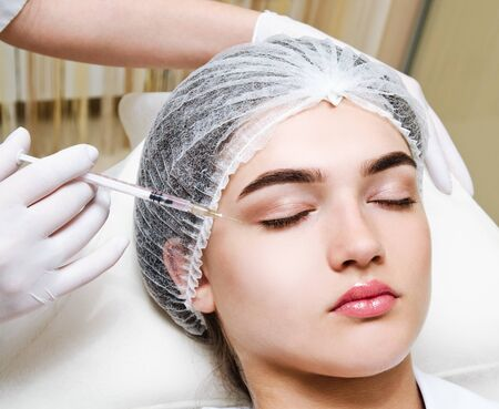 The doctor cosmetologist beautician makes the rejuvenating facial  injections