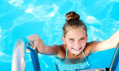 Cute smiling little girl child having fun in the swimming pool on summer vacation Archivio Fotografico