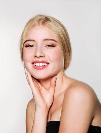 Portret pięknej uśmiechniętej blondynki młodej kobiety twarz. Spa model dziewczyna ze świeżą czystą skórą na białym tle na białym tle. Koncepcja pielęgnacji skóry i włosów
