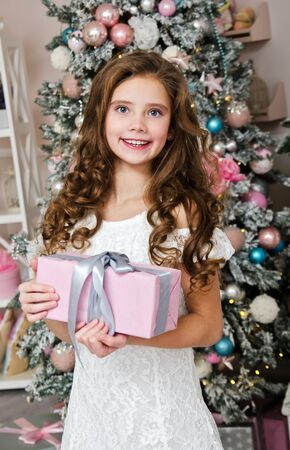 Adorable happy smiling little girl in princess dress with gift box in christmas time