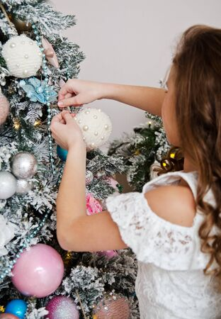 Adorable happy smiling little girl in princess dress  hanging up the balls on fir tree in christmas time Stock Photo