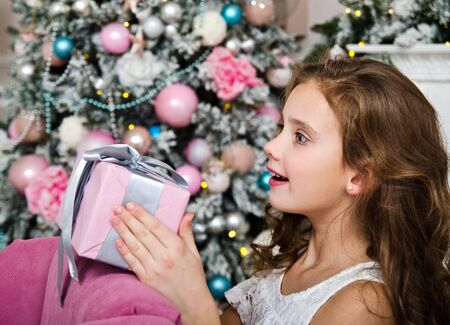 Portrait of adorable happy surprised  little girl child holding gift box near fir tree in christmas time Stock Photo - 130809441