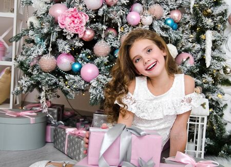Portrait of adorable happy smiling little girl child in princess dress with gift boxes sitting near fir tree in christmas time Stock Photo