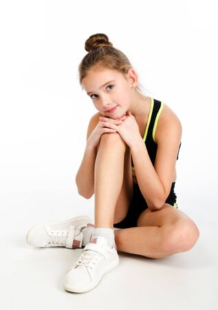 Gymnast smiling little girl child sitting on a floor isolated on white background. Sport, training, fitness, active lifestyle concept