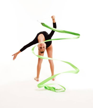 Flexible cute little girl child gymnast doing acrobatic exercise with ribbon isolated on a white background. Sport, training, fitness, active lifestyle concept
