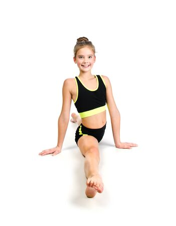 Flexible cute little girl child gymnast doing acrobatic exercise isolated on a white background. Sport, training, fitness, active lifestyle concept