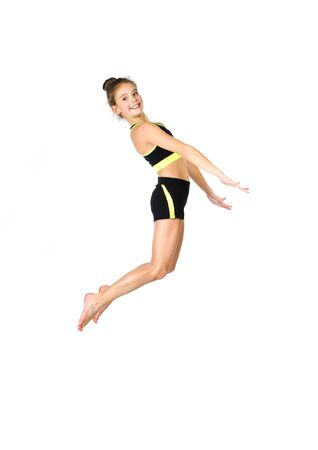 Flexible cute little girl child gymnast jumping and having fun isolated on a white background. Sport, training, fitness, active lifestyle concept