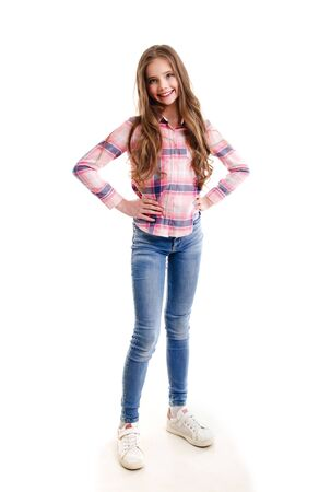 Portrait of adorable smiling little girl child preteen standing in jeans isolated on a white background